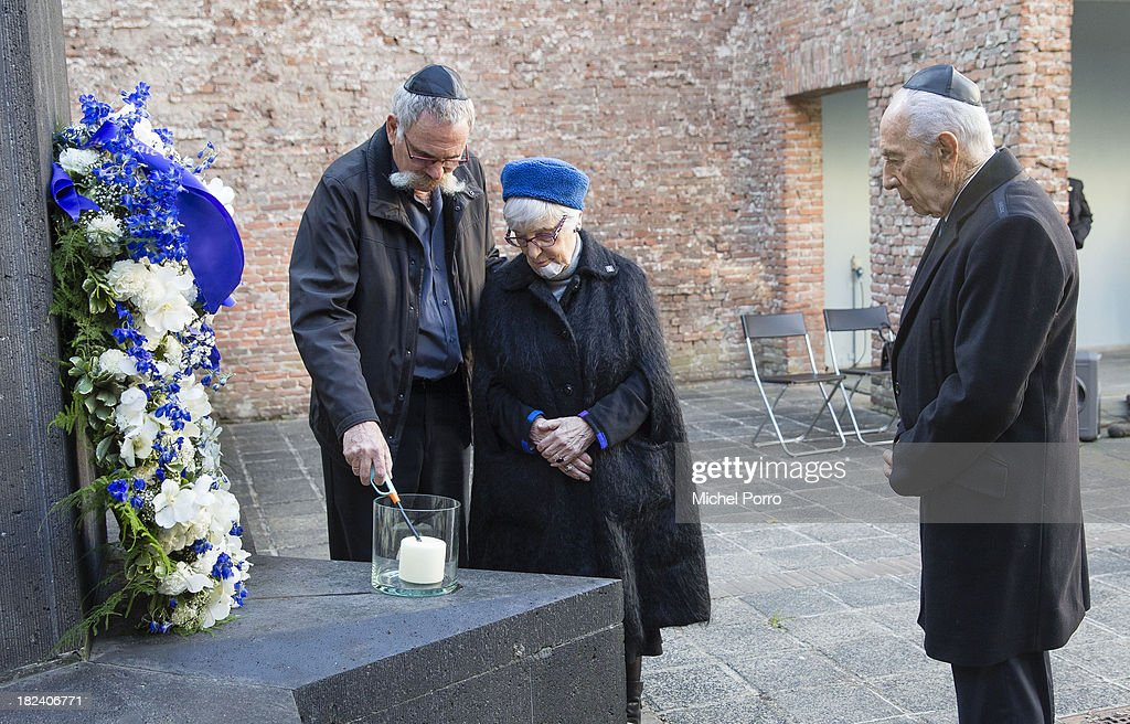 Jossef Avi Yair Engel and holocaust survivor Stelly Menco Ricardo burn a candle in presence of visiting Israeli President <a gi-track='captionPersonalityLinkClicked' href=/galleries/search?phrase=Shimon+Peres&family=editorial&specificpeople=201775 ng-click='$event.stopPropagation()'>Shimon Peres</a> at the Dutch Theatre (Hollandsche Schouwburg) on September 29, 2013 in Amsterdam, Netherlands. The theatre was used as a location to deport Jews in the second World War and is now a monument. Peres is on an official four day visit to the Netherlands.