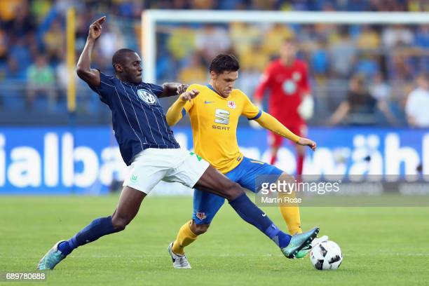 Josuha Guilavogui of Wolfsburg is challenged by Mirko Boland of Braunschweig during the Bundesliga Playoff leg 2 match between Eintracht Braunschweig...