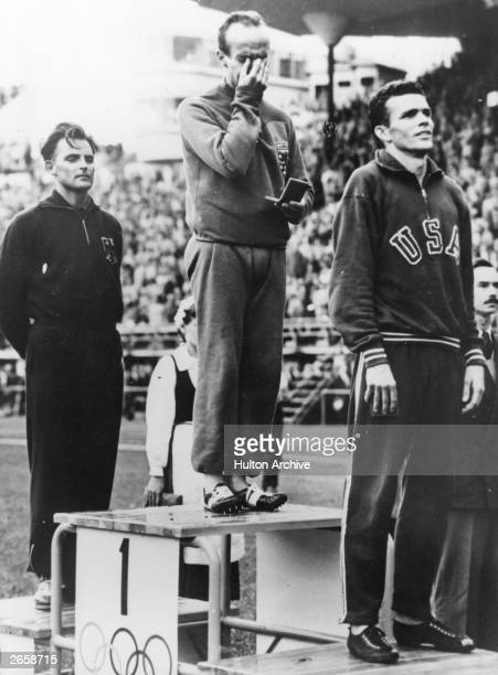 Josy Barthel of Luxembourg weeps for joy during the playing of his national anthem as he stands on the winner's rostrum after winning the 1500 metres...