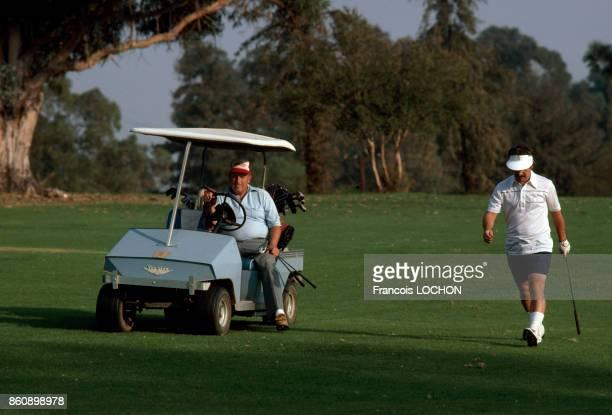 Joueurs et voiture électrique sur un terrain de golf en octobre 1980 EtatsUnis