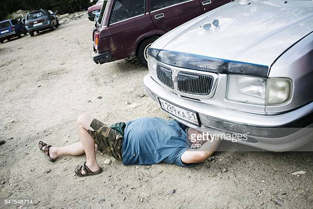 Jouni Huhtala from Kankaanpää tries to pop the hood of his newlybought Volga as asylum seekers' abandoned cars are auctioned in Salla northern...