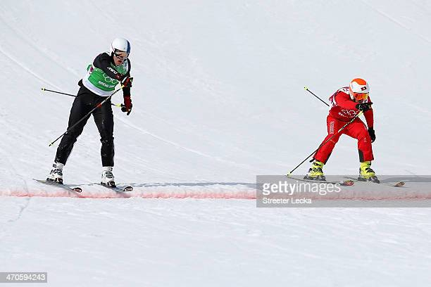 Jouni Pellinen of Finland crosses the line ahead of Armin Niederer of Switzerland during the Freestyle Skiing Men's Ski Cross 1/8 Finals on day 13 of...