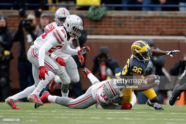 Jourdan Lewis of the Michigan Wolverines is tackled by Dante Booker of the Ohio State Buckeyes on a kick return in the first half at Michigan Stadium...