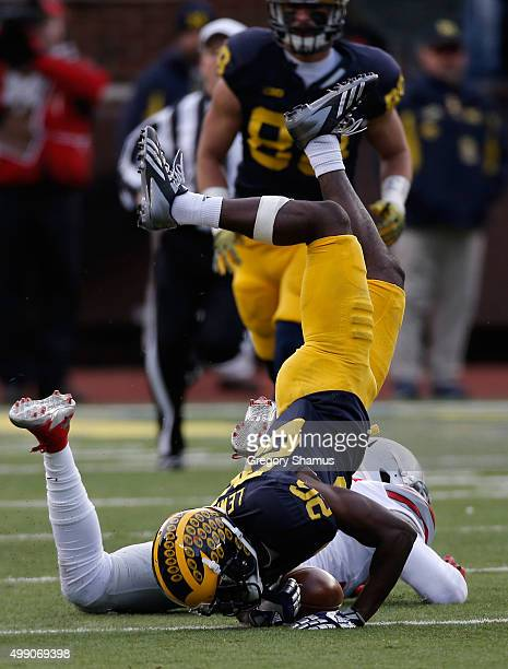 Jourdan Lewis of the Michigan Wolverines is tackled in the fourth quarter against the Ohio State Buckeyes at Michigan Stadium on November 28 2015 in...