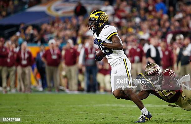 Jourdan Lewis of the Michigan Wolverines tries to avoid the tackle of Carlos Becker III of the Florida State Seminoles in the first half during the...