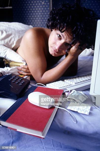 Journalist and editor James Brown lies in bed with an Apple Macintosh computer a bottle of champagne and a phone London United Kingdom 1997 Brown...