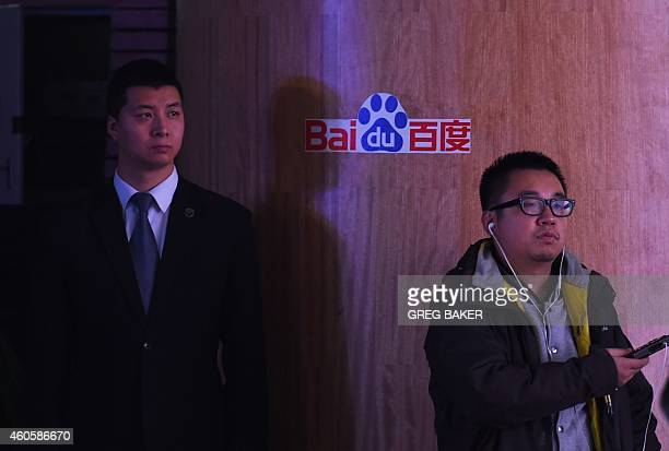 A journalist and security guard stand near a Baidu logo during a press conference at the Baidu headquarters in Beijing on December 17 2014 Baidu...