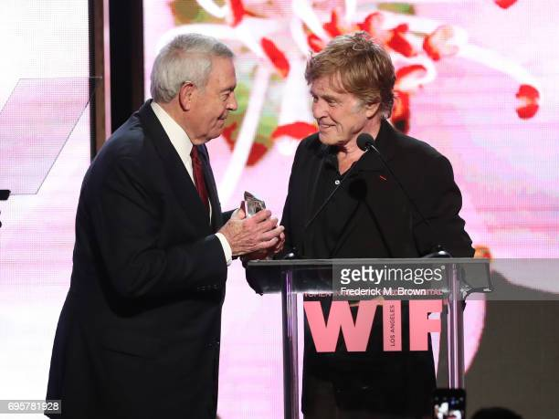 Journalist and The Norma Zarky Humanitarian Award Honoree Dan Rather receives award onstage from actor Robert Redford at the Women In Film 2017...