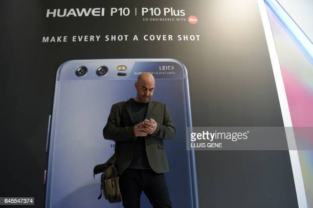 A journalist checks his mobile in front of a billboard announcing the new model of Chinese multinational networking and telecommunications equipment...