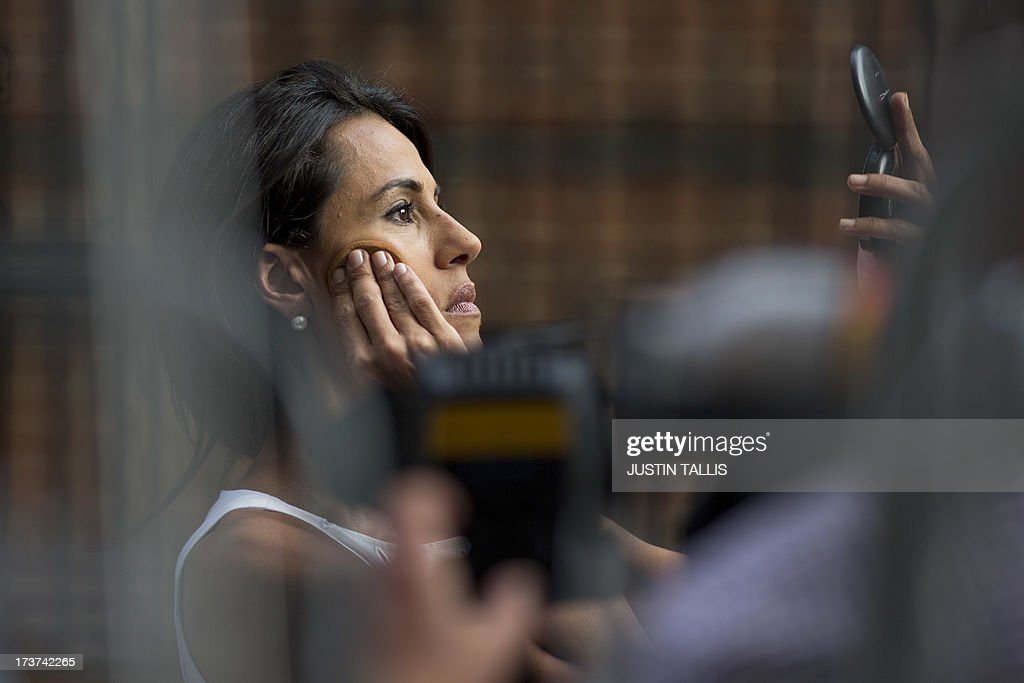 A TV journalist does her make up before recording a piece to camera outside the Lindo Wing of Saint Mary's Hospital in London, on July 17, 2013, where Prince William and his wife Catherine's baby will be born. Queen Elizabeth II, it seems, is just as impatient as her subjects for the royal baby to arrive this week -- because she is going on holiday. AFP PHOTO / JUSTIN TALLIS