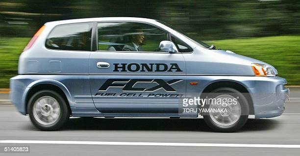 A journalist drives a prototype of fuel cell vehicle FCX of Japan's automaker Honda Motor Co Ltd during a press preview in Tokyo 24 October 2002 The...