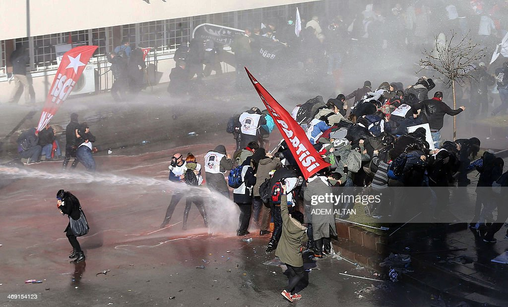 A journalist (L) ducks as riot police use tear gas and a water cannon to disperse protesters trying to march to the parliament building in Ankara during a demonstration against the Turkish prime minister and Turkey's ruling Justice and Development Party (AKP) on February 13, 2014. Turkish riot police on February 13 fired tear gas and water cannon at around 2,000 protesters demanding the release of army officers jailed for plotting a coup. At least 12 protesters were arrested and two people, including a police officer, were injured in clashes.