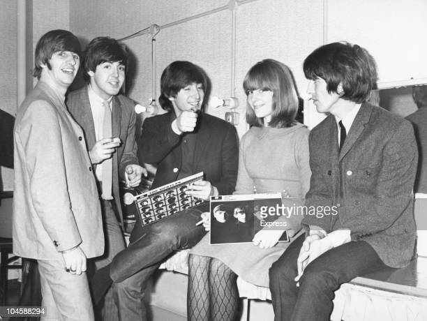 Journalist Elizabeth Freeman sits with band The Beatles from left to right Ringo Starr Paul McCartney John Lennon and George Harrison November 2 1964