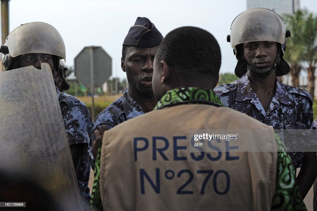 A journalist faces security forces, as they stand to prevent a crowd of several hundred journalists and members of the public from protesting in front of the Palais des Congres in Lome on February 19, 2013. Journalists in Togo are protesting against a law giving the High Authority of Audiovisual and Communication (HAAC) more power to control media in Togo.
