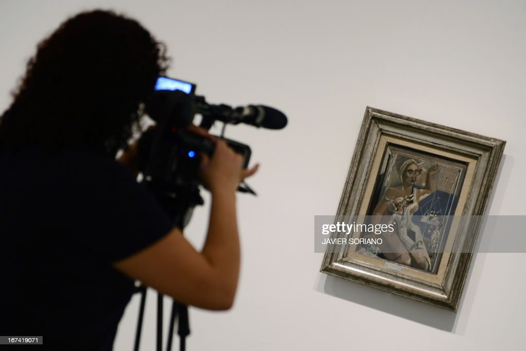 A journalist films a painting entitled 'Departure. Homage to the Noticiario Fox' (1926) by Spanish surrealist artist Salvador Dali during the exhibition 'Dali. All of the poetic suggestions and all of the plastic possibilities' at the Reina Sofia museum in Madrid on April 25, 2013.
