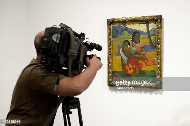 A journalist films Paul Gauguin's artwork 'Nafea Ipoipo faa' the most expensive painting ever sold at the Reina Sofia Museum in Madrid on July 3 2015...