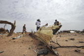 A journalist films the crash site of the Air Algerie Flight AH 5017 in Mali's Gossi region west of Gao on July 26 2014 UN experts investigating the...