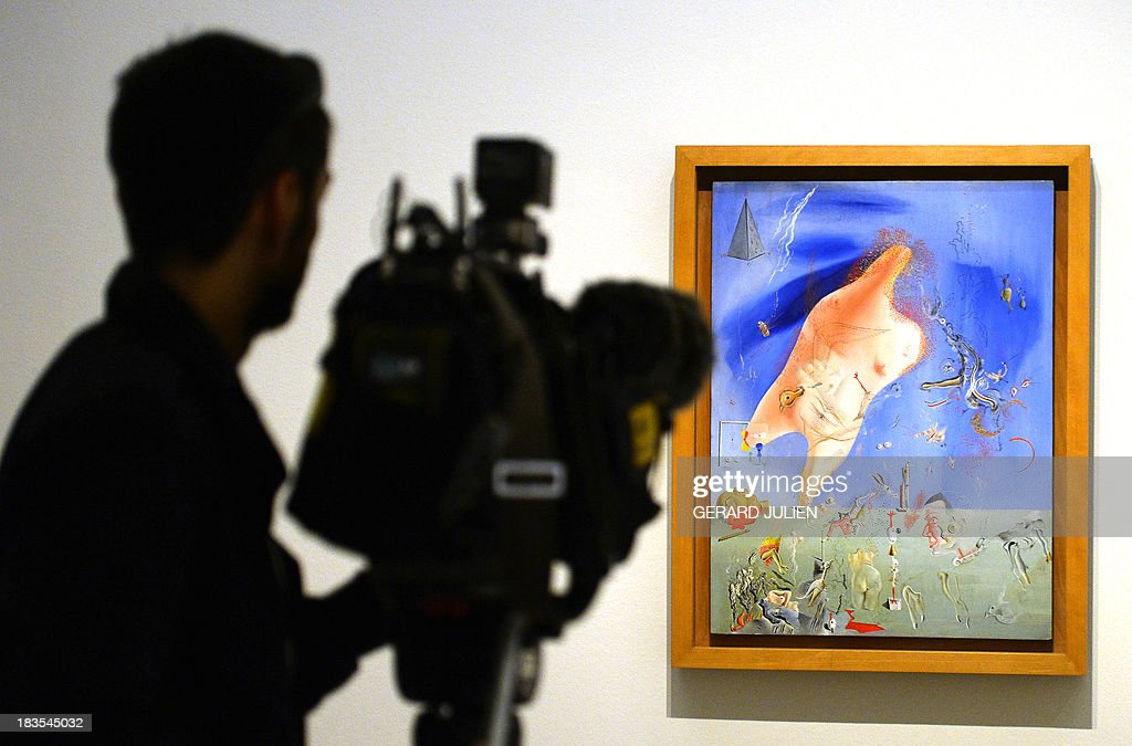 A journalist films the painting 'Los esfuerzos esteriles' by Salvador Dali during the exhibition entitled 'Surrealism and the Dream' at the Thyssen-Bornemisza museum in Madrid, on October 7, 2013.