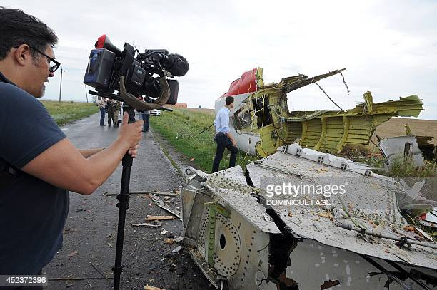 A journalist films the site of the crash of a Malaysia Airlines plane carrying 298 people from Amsterdam to Kuala Lumpur in Grabove in rebelheld east...