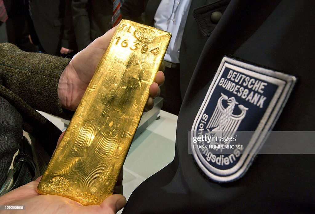 A journalist holds a bar of gold during a press conference at the German Federal Bank in Frankfurt am Main, western Germany, on January 16, 2013.The German central Bundesbank said it will relocate parts of its gold stored abroad following recent accusations that it is not keeping proper track of its vast reserves.