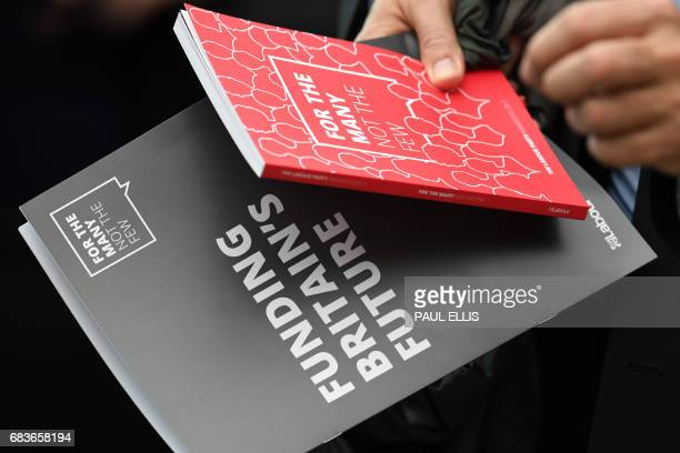 A journalist holds a copy of the opposition Labour party election manifesto at its launch in Bradford on May 16 2017 / AFP PHOTO / Paul ELLIS