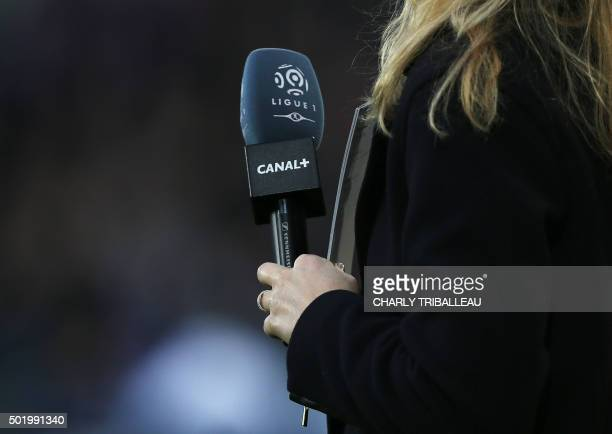 A TV journalist holds a microphone with the logo of French first football division Ligue 1 and Canal plus before the French L1 football match between...