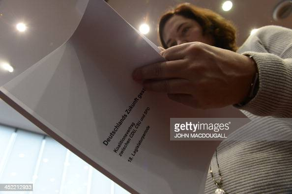 A journalist holds a print of the agreement to form a coalition government to be signed by Christian Democratic Party Bavarian allies Christian...