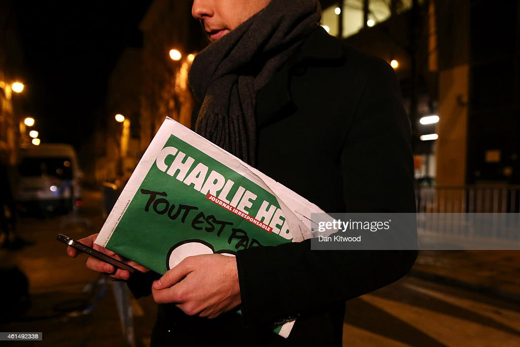 A journalist holds an early copy of a Charlie Hebdo magazine while delivering a news report outside the offices of Liberation Newspaper Group on January 13, 2015 in Paris, France. Three million copies of the controversial magazine have been printed and are due to be released tomorrow, in the wake of last weeks terrorist attacks.
