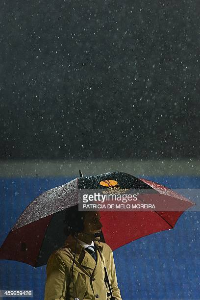 A journalist holds an umbrella under heavy rain during the UEFA Europa League Group E football match Estoril Praia vs PSV Eindhoven at Antonio...