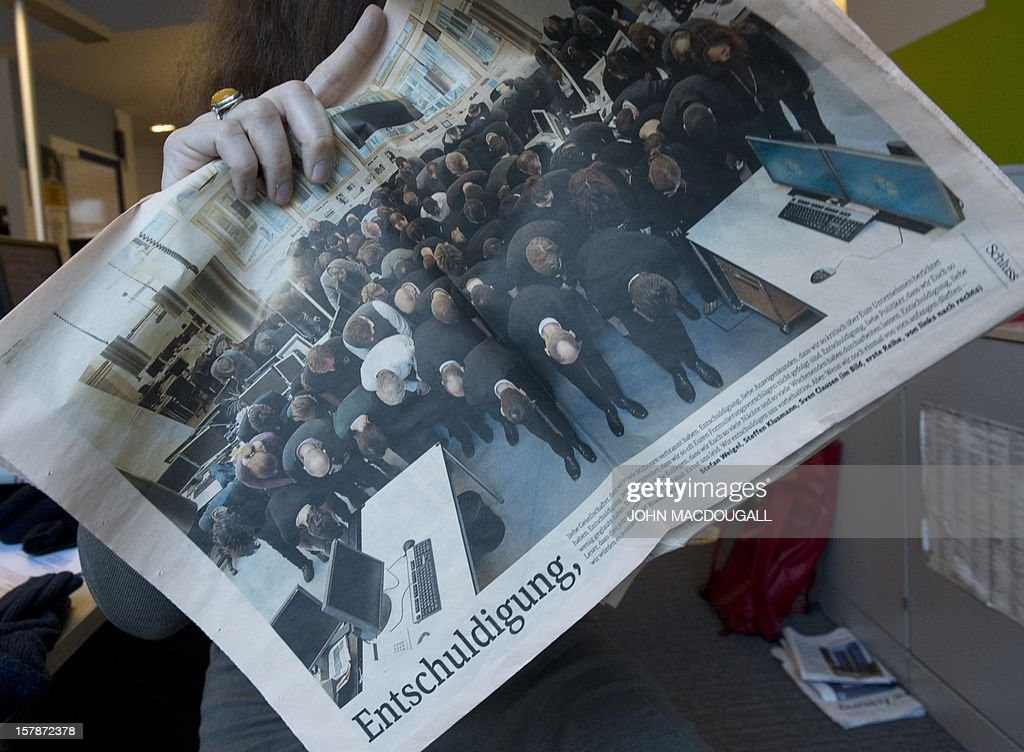 A journalist holds up a copy of the last edition of the German business daily Financial Times Deutschland (FTD) in Berlin on December 7, 2012. FTD, launched 12 years ago as the German-language sister of the Financial Times, blacked out its front page to mark its last day of publication, titeling 'Finally in the black'. On the back page all of the newspaper's staff were pictured bowing their heads in mock hara-kiri style penitence. MACDOUGALL