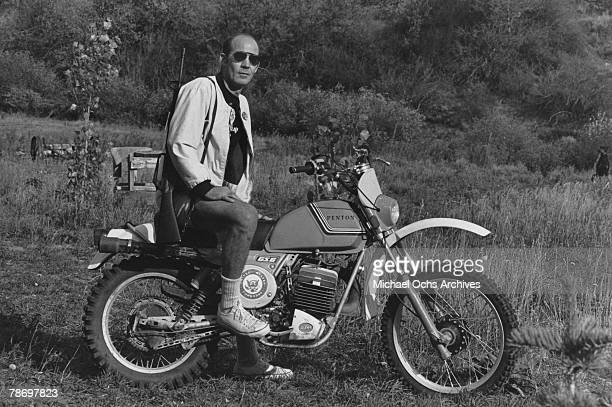 Journalist Hunter S Thompson sits on his Penton Motor Cycle with his rifle over his shoulder on his ranch circa 1976 near Aspen Colorado