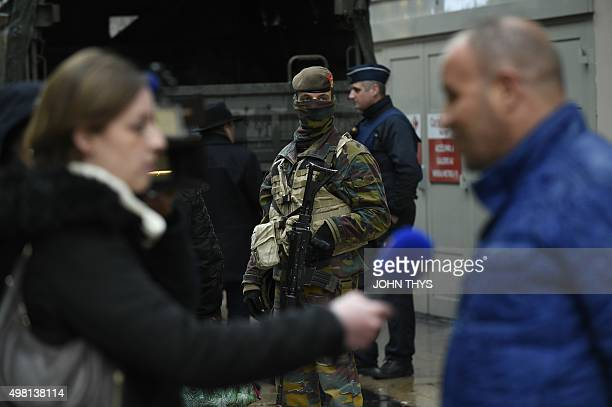 A journalist interviews a man as a soldier patrols the Rue Neuve pedestrian shopping street in Brussels on November 21 2015 All metro train stations...