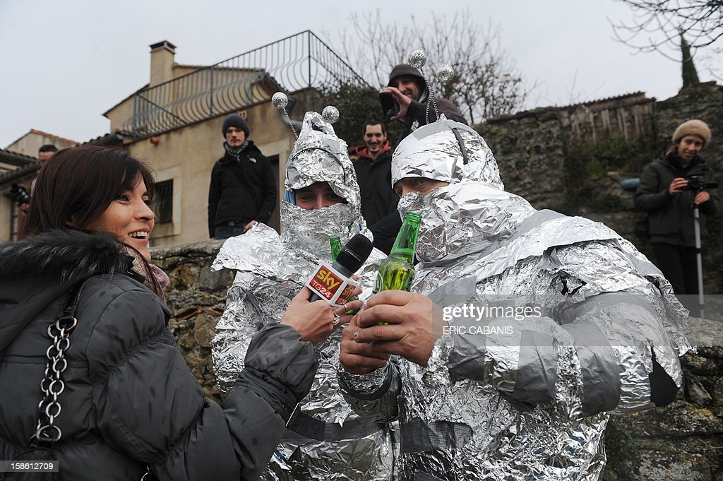 A TV journalist interviews men disguised in 'martians' on December 21, 2012, in the street of the French southwestern village of Bugarach, near the 1,231 meter high peak of Bugarach - one of the few places on Earth some believe will be spared when the world allegedly ends today according to claims regarding the ancient Mayan calendar. French authorities have pleaded with New Age fanatics, sightseers and media crews not to converge on the tiny village.