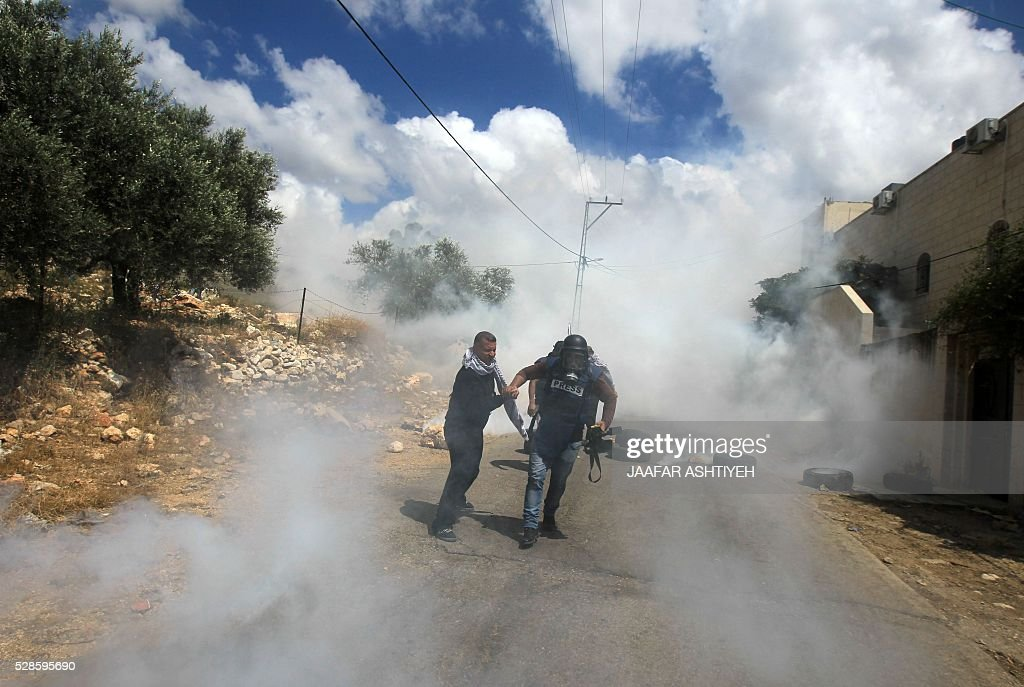 A journalist is helped by Palestinian man as he runs for cover from tear gas fired by Israeli security forces during clashes with Palestinian protesters following a weekly demonstration against the expropriation of Palestinian land by Israel in the village of Kfar Qaddum, near Nablus, in the occupied West Bank, on May 6, 2016. / AFP / JAAFAR