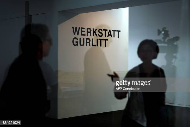 A journalist is seen in silhouette gesturing at the entrance of the Gurlitt Workshop during a press preview of the restauration studio at the Museum...