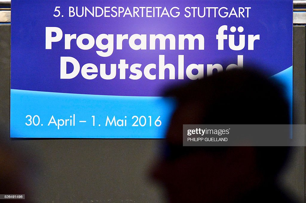 A journalist is silhouetted against a poster reading 'Programme for Germany' during a party congress of the German right wing party AfD (Alternative fuer Deutschland) at the Stuttgart Congress Centre ICS on April 30, 2016 in Stuttgart, southern Germany. The Alternative for Germany (AfD) party is meeting in the western city of Stuttgart, where it is expected to adopt an anti-Islamic manifesto, emboldened by the rise of European anti-migrant groups like Austria's Freedom Party. / AFP / Philipp GUELLAND