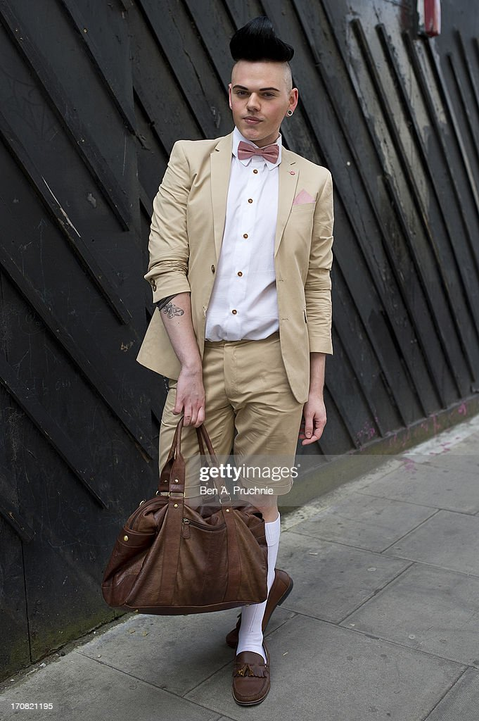 Journalist Josh St James (25) poses wearing a Topman suit with a Vivienne Westwood blazes with an ASOS bag and Topshop shoes at the James Long catwalk presentation held at the Old Sorting Office during London Collections:MEN SS14 on June 18, 2013 in London, England.