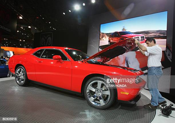 A journalist lifts the hood of the Dodge Challenger R/T at a preview on March 19 2008 at the New York International Auto Show AFP PHOTO/Stan HONDA