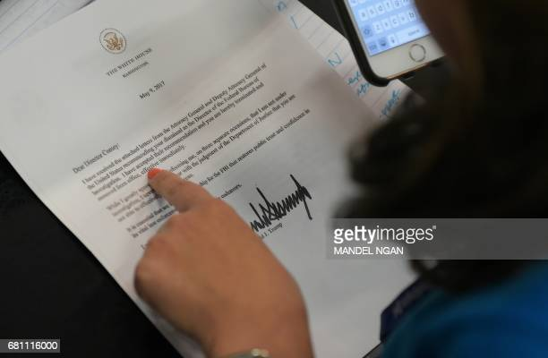 A journalist looks at a copy of the termination letter to FBI Director James Comey from US President Donald Trump in the Brady Briefing Room of the...
