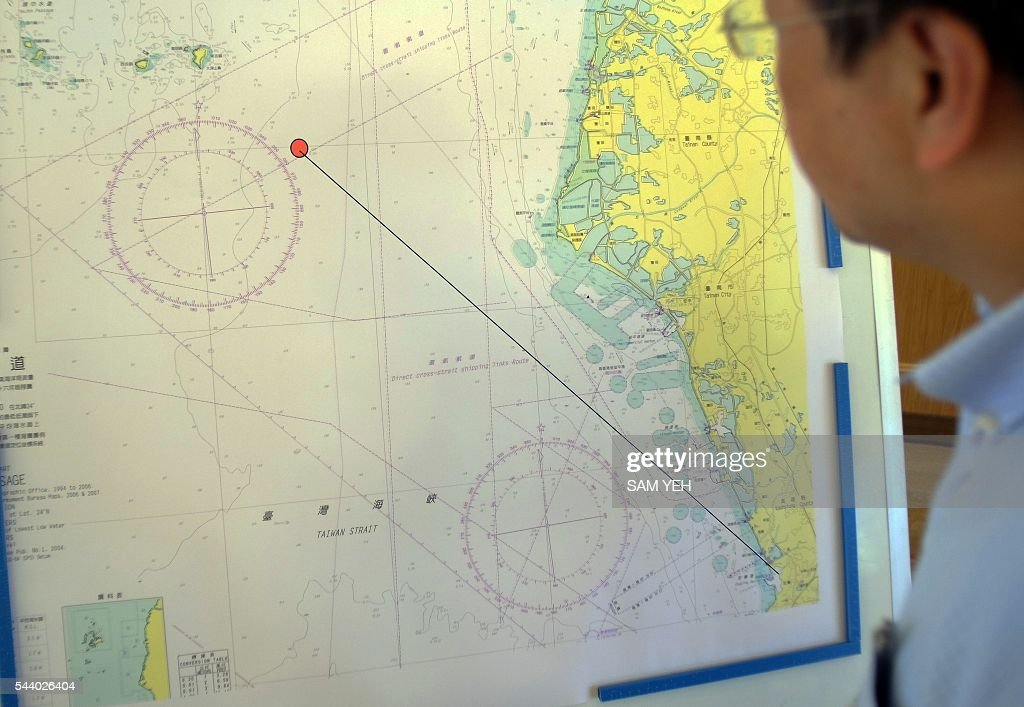 A journalist looks at a map showing the misfired missile route during a press conference in Taipei on July 1, 2016. Taiwan's military authorities said a lethal anti-ship missile was 'mistakenly' launched and fell into the Taiwan Strait as ties between the island and former bitter rival China deteriorate. / AFP / SAM YEH