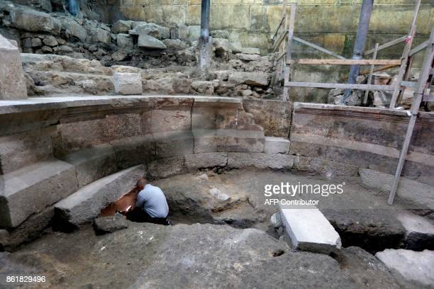 A journalist looks at part of a recently discovered ancient roman theatre from the second sanctuary that was found by the Israeli Antiquity Authority...