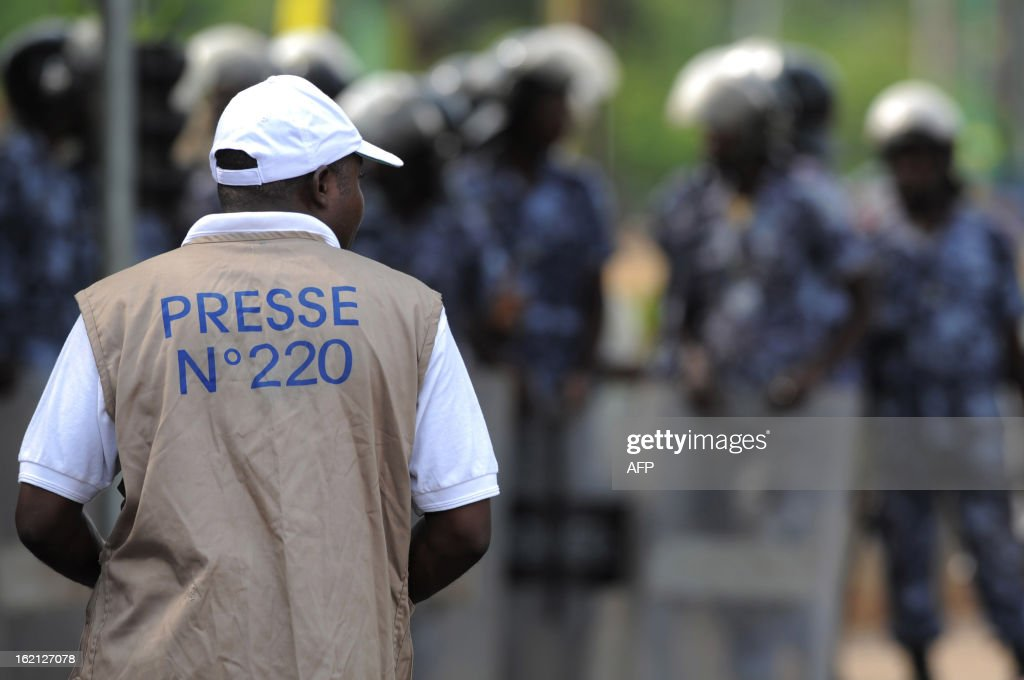 A journalist looks at security forces standing to prevent a crowd of several hundred journalists and members of the public from protesting in front of the Palais des Congres in Lome on February 19, 2013. Journalists in Togo are protesting against a law giving the High Authority of Audiovisual and Communication (HAAC) more power to control media in Togo.