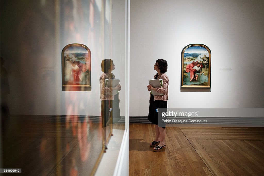 A journalist looks at works of Dutch painter Hieronymus Bosch during a press preview at El Prado Museum on May 27, 2016 in Madrid, Spain. The Prado Museum holds the 'El Bosco' (Hieronymus Bosch) painter major exhibition to celebrate the fifth century anniversary of the Dutch artist's death (ca. 1450-1516) featuring sixty five works from various Spanish and global museums.