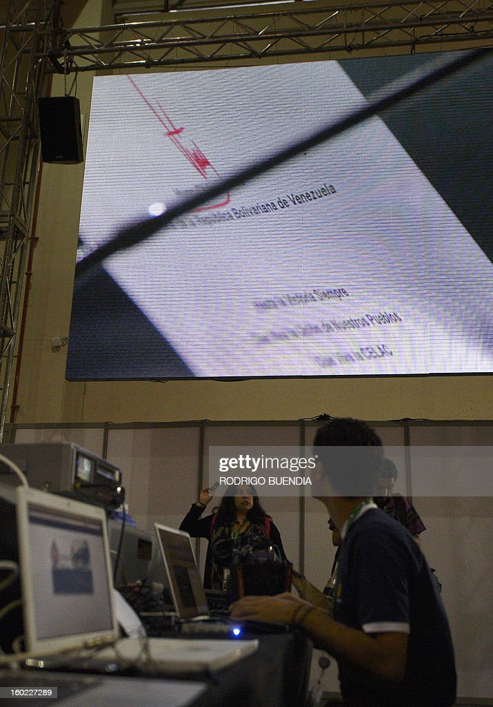 A journalist looks on a screen at the signature of Venezuelan President Hugo Chavez seen on the bottom of a message sent by him and being read by Venezuelan Vice-President Nicolas Maduro during a plenary session of the Latin American and Caribbean States (CELAC) Summit in Santiago, on January 28, 2013. After wrapping up talks with their European counterparts, Latin American leaders on Sunday opened their own summit, with the event notable for the absence of Chavez.