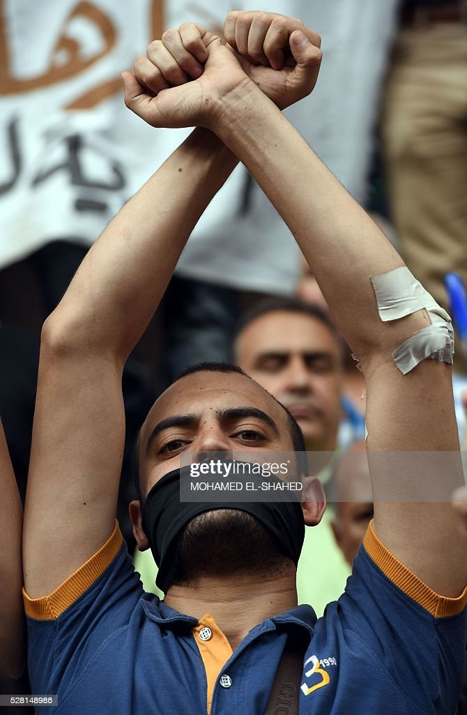 A journalist makes a gesture symbolising a detention during a demonstration outside the Journalist Syndicate headquarters in Cairo calling for the sacking of the interior minister following an unprecedented police raid to arrest two reporters on May 4, 2016. / AFP / MOHAMED