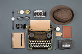 Journalist or private detective workplace - typewriter, camera, hat, recorder and other stuff, flat view above