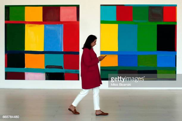 A journalist passes some paintings by Stenley Whitney at a preview of Documenta 14 on April 7 2017 in Athens Greece Documenta 14 is an exhibition of...