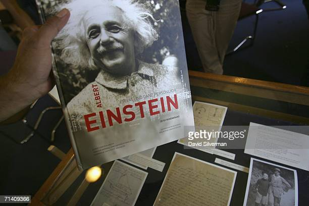 A journalist picks up a book on Albert Einstein during a press conference displaying newlyrevealed letters and photos from the Albert Einstein...