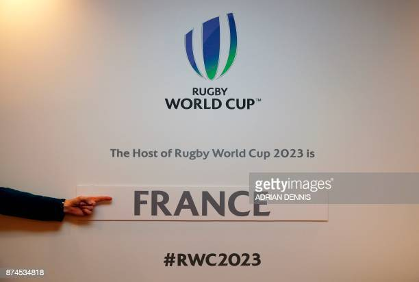 A journalist points to the France sticker attached to the wall after being named host for the 2023 Rugby World Cup in London on November 15 2017...