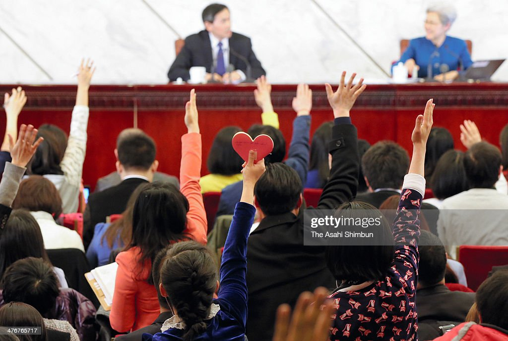 A journalist raises her hand with heart-shape memopad to draw attention during a press conference ahead of the National People's Congress (NPC) at the Great Hall of the People on March 4, 2014 in Beijing, China.